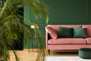 Green living room with pink sofa