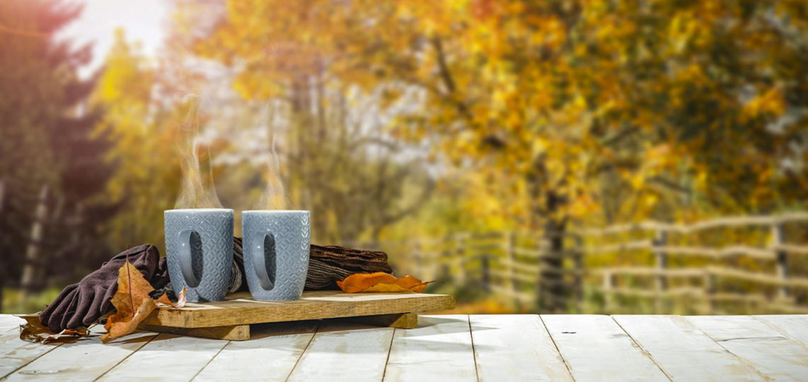 Two mugs of a hot drink sitting on a wooden board with an autumnal garden in the background