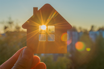 A person holding up a cardboard cut out of a house in a field while the sun shines through the cutout